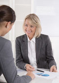 Two business woman sitting at desk: customer and adviser talking — Stock Photo