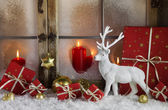 Festively christmas decoration with red gifts and a white reinde — Stock Photo