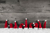 Wooden christmas background with red santa hats for a festive fr — Stockfoto
