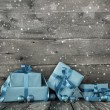 Grey wooden christmas background with a stack of presents in blu — Stock Photo #56034199