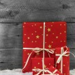 Red christmas presents on wooden background with snow. — Stock Photo #56034795