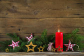 Christmas decoration: red candle and brunches on wooden old back — Stock Photo