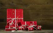 Red christmas presents on an old wooden brown background. — Stock Photo