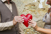 Valentine's day: couple holding red heart in her hands. — Stock Photo