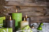 Four burning apple green christmas candles on wooden background. — Stock Photo