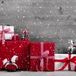 Red Christmas presents and gift boxes with rocking horse on grey — Stock Photo #57079815