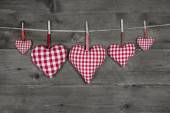 Five handmade red checkered hearts on wooden grey background. — Foto de Stock