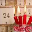 Four red burning advent candles with calendar. — Stock Photo #57085335