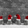 Grey festive wooden christmas background with four santa hats on — Foto Stock #57085443