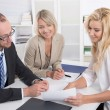 Business team of man an woman sitting around a table talking tog — Stock Photo #57684375