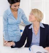 Friendly atmosphere at work: two smiling businesswoman. — Stock Photo