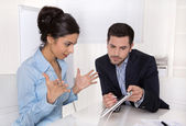 Amazed businesswoman in blue with her boss looking at tablet scr — Stock Photo