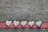 Five white hearts on an old grey wooden background with a checke — Stock Photo
