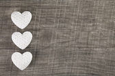 Three white hearts on an old grey brown wooden background. — Stock Photo