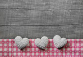 Greeting card: three white and pink checked hearts on wooden gre — Stock Photo