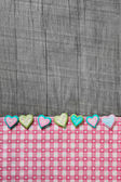 Shabby chic grey wooden background with hearts on a pink white c — Stock Photo