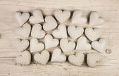 Beige or old white hearts on wooden shabby chic background. — Stock Photo