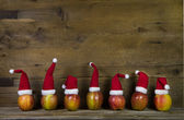 Funny christmas greeting card with seven red santa hats on apple — Stock Photo