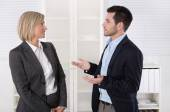 Two business people working in a team talking together in the of — Stock Photo