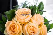 Orange roses bunch with wedding rings. — Stock Photo