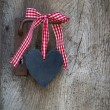 Black heart with a red white checked ribbon hanging on an old do — Stock Photo #68150295