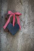 Black heart with a red white checked ribbon hanging on an old do — Stock Photo