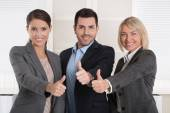 Thumbs up: three successful business people of man and woman in  — Stock Photo