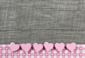 Wooden grey shabby chic background with pink hearts on a white r — Stock Photo