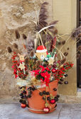 Outdoor christmas decoration with a teddy santa and dry plants. — Stock Photo