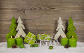 Four green burning christmas candles with presents and trees on — Stock Photo