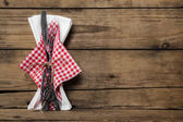 Fork and knife set with red white checked napkin on old rustic w — Stock Photo