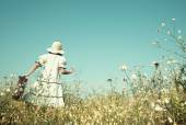 Girl on the way to her future walking in a flowery meadow with h — Stock Photo