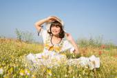 Happy young girl sitting in a flowery meadow in summertime. — Stock Photo