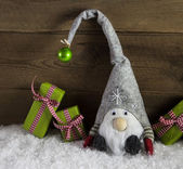 Gnom santa with green and red christmas presents in rustic count — Stock Photo
