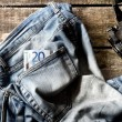 Pair of dirty jeans, twenty euro bill and vintage camera — Stock Photo #53412029