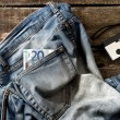 Pair of dirty jeans, twenty euro bill and vintage camera — Stock Photo #53412033