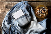 Pair of dirty jeans,notepad and an ashtray — Foto de Stock