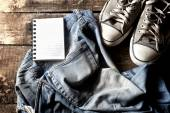 Dirty jeans, notepad and sneakers — Stock Photo