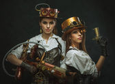 Two girls dressed in the style of steampunk with arms — Stock Photo