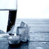 Sklenice vody a tání ledu na dřevěný stůl. — Stock fotografie