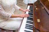 Bride plays piano — Stock Photo