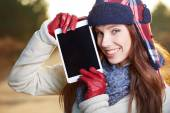 Close up of happy beautiful woman show on tablet pc in the park — Stock Photo