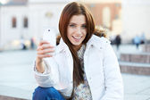Pretty young woman taking a picture on town. Smiling girl. Winte — Stock Photo