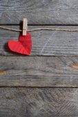 Red heart hanging on the clothesline. On old wood background. — Stock Photo