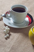 Cup of hot drink with coffee beans — Stock Photo
