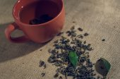 Dry tea with green leaves in cup, on burlap background — Stockfoto