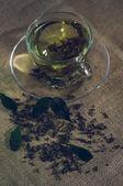 Hojas de té seco con verde en Copa, en el fondo de arpillera — Foto de Stock