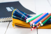 Sketchbook and colorful pencils on the table — Fotografia Stock