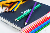 Sketchbook and colorful pencils on the table — Stock Photo
