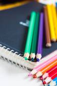 Sketchbook and colorful pencils on the table. — Stock Photo